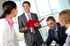 Image of businessman answering questions of colleagues at meeting Stock Photos