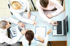 Above view of four businesswomen sitting at table and pointing at the laptop scr Stock Photos