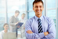 Business leader looking at camera with team of partners working in office behind Stock Photos