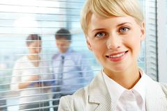 female leader looking at camera with two partners interacting in office behind - stock photo