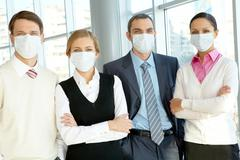 portrait of business team in protective masks looking at camera - stock photo