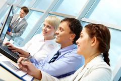 portrait of working partners looking at laptop monitor in office and interacting - stock photo