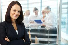Portrait of pretty female looking at camera with smile in office Stock Photos