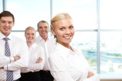 portrait of pretty blonde looking at camera with colleagues on background - stock photo