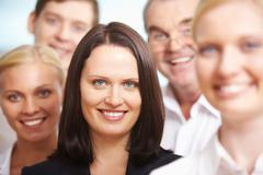 portrait of pretty female looking at camera surrounded by her colleagues - stock photo