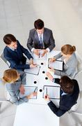 Stock Photo of above view of friendly workteam discussing new ideas at meeting