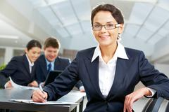 portrait of pretty woman looking at camera in working environment - stock photo