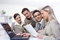 four young businesswomen sitting at table with a laptop and examining a document - stock photo