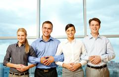 row of young partners crossing arms and looking at camera - stock photo