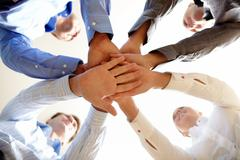 Below shot of four co-workers making pile of hands Stock Photos