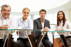 image of confident business team sitting at a glassy table - stock photo