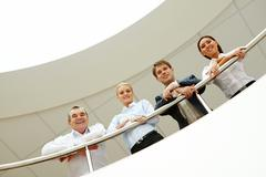Business team with smiles leaned on the handrail Stock Photos