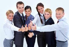 Portrait of friendly business team showing thumbs up and looking at camera Stock Photos