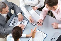Neljä liikenaiset istuu pöydässä tutkii joitakin asiakirjoja Kuvituskuvat