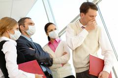 group of associates in protective masks looking strictly at coughing man - stock photo