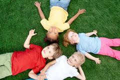 Image of little boys and girls lying on green grass and looking up Stock Photos