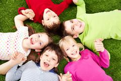 image of smiling young boys and girls playing on the grass - stock photo