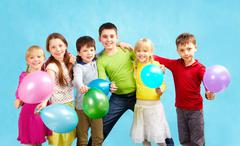 Portrait of smiling children holding balloons and embracing each other Stock Photos