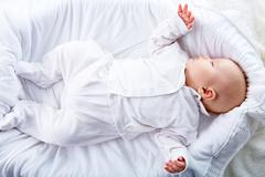 above view of baby lying in comfortable cradle at home - stock photo