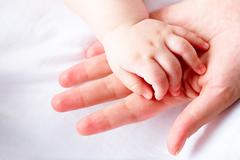 image of newborn baby hand over female palm - stock photo