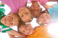 Below view of happy children embracing each other and smiling at camera Stock Photos