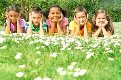 portrait of cute kids lying on green grass and looking at camera - stock photo