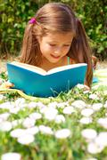 Portrait of cute schoolgirl reading interesting book in natural environment Stock Photos