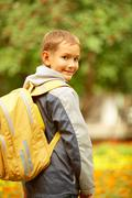 Portrait of happy lad with rucksack on back looking at camera on his way to scho Stock Photos