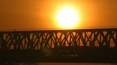 Train on the bridge at sunset. Railroad. - stock footage