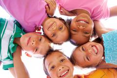 Stock Photo of below view of happy children embracing each other and smiling at camera