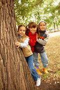 Stock Photo of portrait of happy kids looking at camera while hiding behind tree trunk