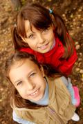 portrait of two happy girls looking at camera with smiles - stock photo