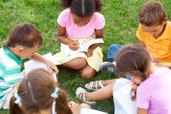 Portrait of cute kids seated on green grass with copybooks and pencils Stock Photos
