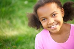 Portrait of cute girl looking at camera and smiling Stock Photos