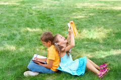 portrait of cute kids seated on green grass with copybooks and pencils and drawi - stock photo