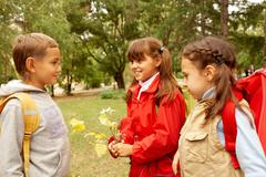 portrait of schoolchildren chatting in autumnal park - stock photo