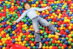 Stock Photo of happy lad seated on colorful balls and looking at camera with smile