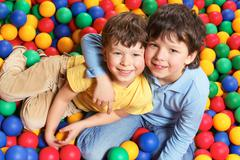 happy lad embracing his brother and both looking at camera with smiles - stock photo