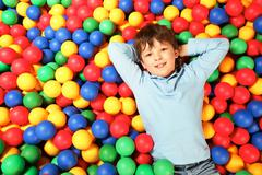 happy lad lying on colorful balls and looking at camera with smile - stock photo