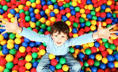 Stock Photo of happy lad seated on colorful balls and stretching arms to camera