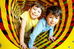 happy siblings looking at camera while having fun inside toy tunnel - stock photo