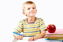 clever schoolboy paying attention to something while drawing - stock photo