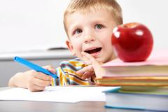 portrait of pensive boy sitting at the table with books on it - stock photo