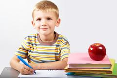 diligent schoolboy looking at camera during drawing - stock photo