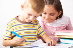 portrait of boy drawing on the paper with curious girl looking at it near by - stock photo