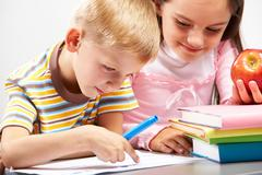 portrait of boy pointing at paper and  girl with apple - stock photo