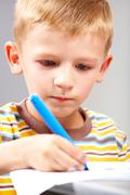 close-up of school boy drawing picture - stock photo