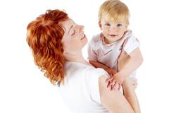 portrait of happy woman holding her small daughter - stock photo