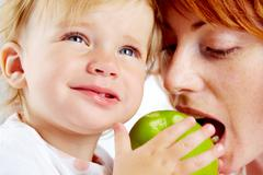 portrait of female ready to bite ripe apple in her child hands - stock photo