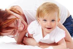 portrait of happy woman playing with her small daughter - stock photo